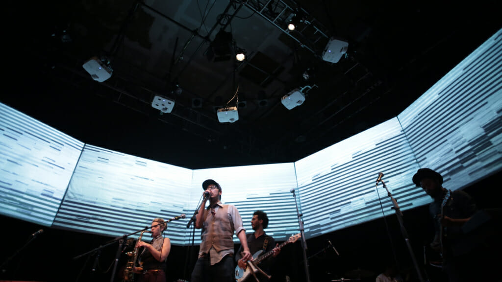 Click to play video. Image shows Four Musicians stand in front of a giant video display with abstract lines.
